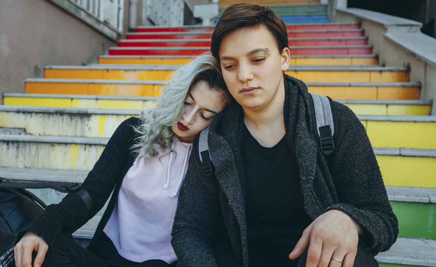 Two teens sitting on a multicolored outdoor stairway looking somber