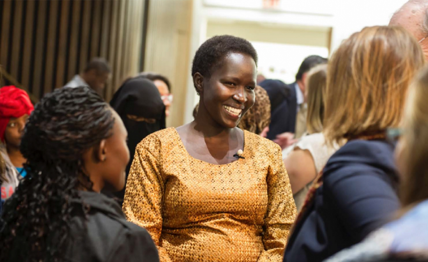 Kakenya Ntaiya, in a gold patterned shirt, stands among a crowd