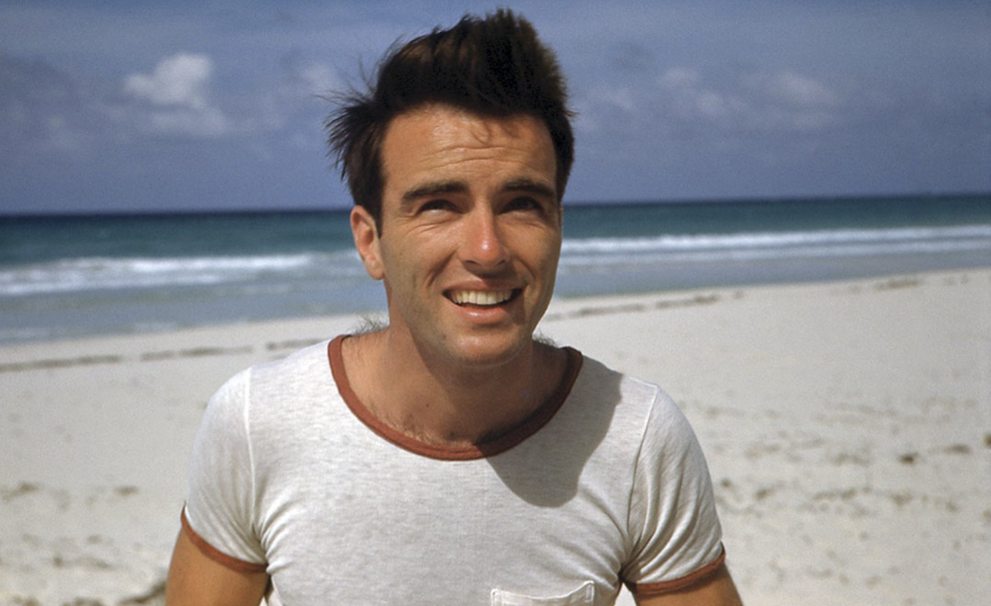 Actor Montgomery Clift wearing white T-shirt with a sandy beach in the background