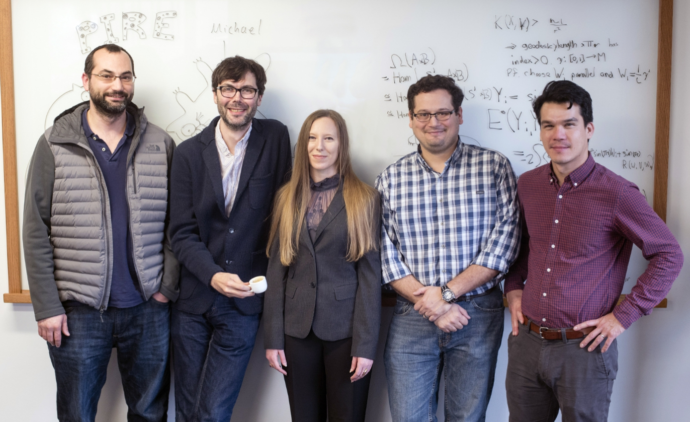 five researchers standing in front of whiteboard with equations and other writing on it