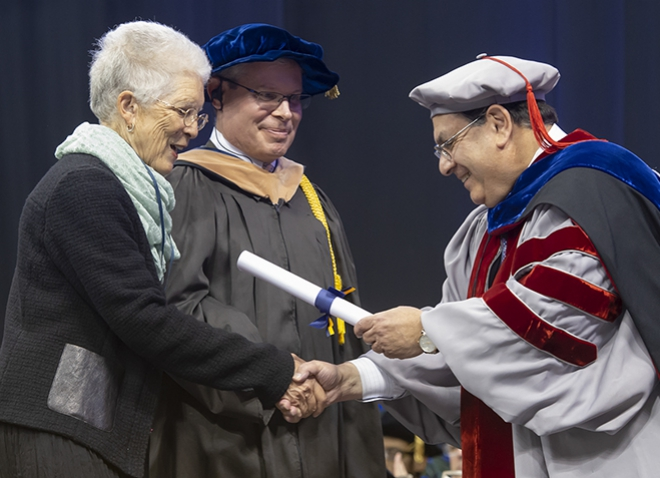 Mary Ellen Butler accepting diploma from business school dean, who is dressed in commencement robes, while another man looks on