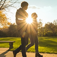 two people walking with a brilliant sun ray behind them