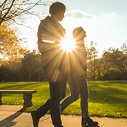 two people walking in front of the sun