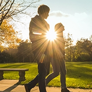 two people walking on campus with the bright sun behind them, obscuring their faces and bodies