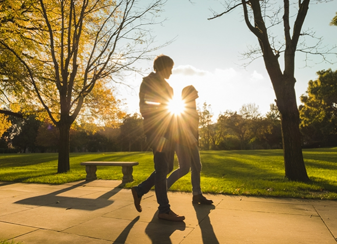 two students walking on the PItt campus, silhouetted by sun