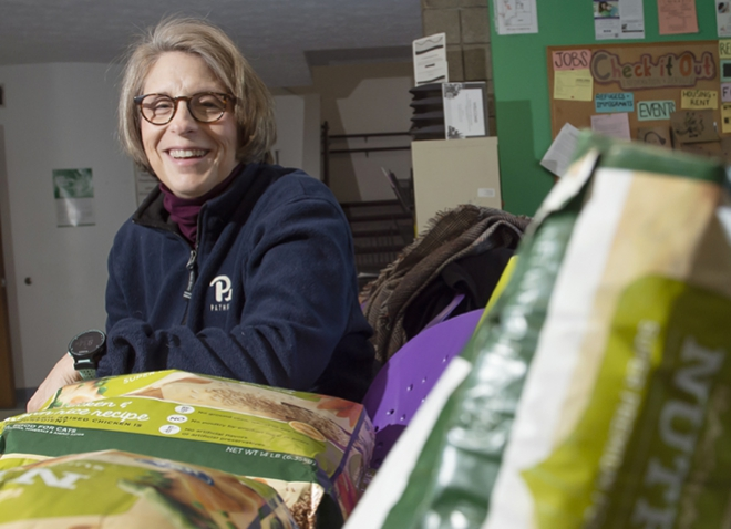 Mary Beth Rautkis wearing blue PItt sweatshirt, photographed with donated bags of pet food at an area food bank