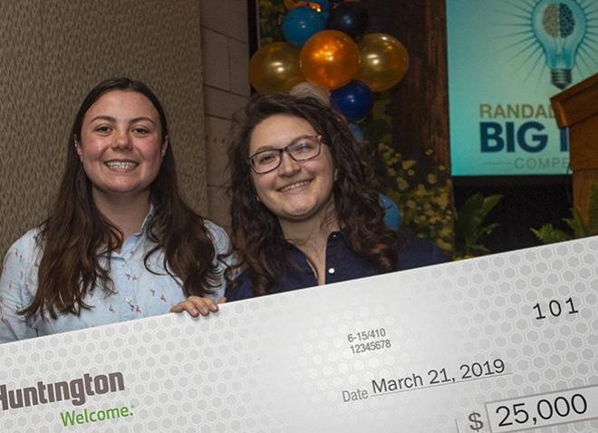 Undergrads Lauren Yocum and Emily Siegel holding giant check for $25,000