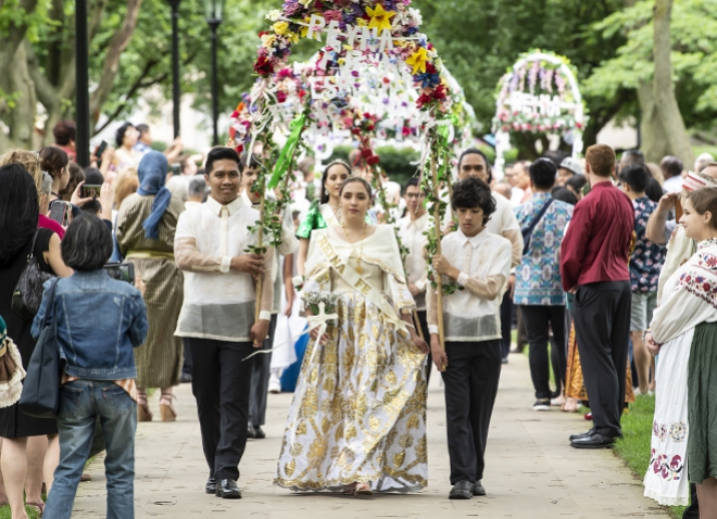 parade of young women walking under arches of flowers held by young men