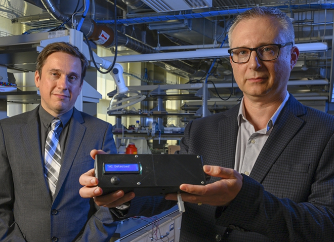 Associate professor of electrical and computer engineering Ervin Sejdic, left, and professor of chemistry Alexander Star pose with the prototype of the THC Breathalyzer developed using their interdisciplinary research.