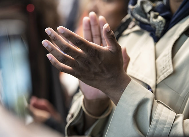 A person in a beige coat clapping