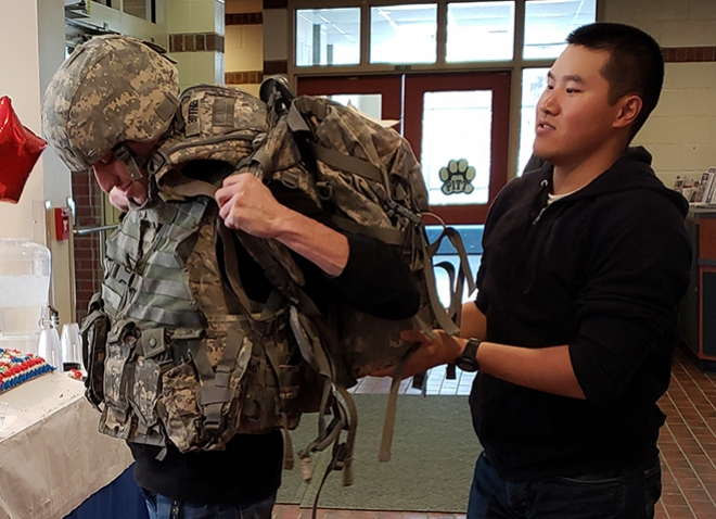 One person helps another into military gear