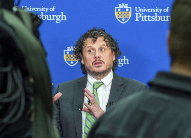 Duprex in a suit and green tie in front of a University of Pittsburgh background