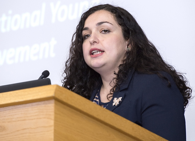 Vjosa Osmani speaking at a podium in a dark top