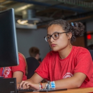 Female student in a red shirt typing on computer keyboard with monitor facing her