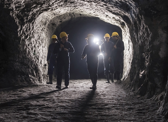 five miners in a cave with a bright light shining behind them