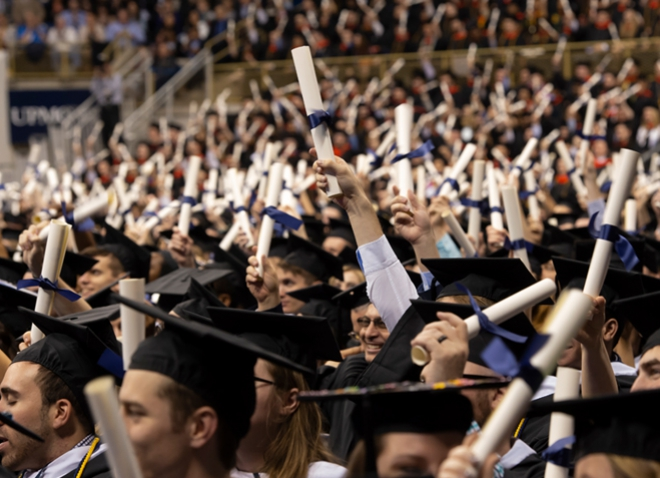 a group of graduates holding scrolls high in the air