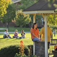 Students sitting out on a lawn and in a gazebo at Pitt Bradford campus