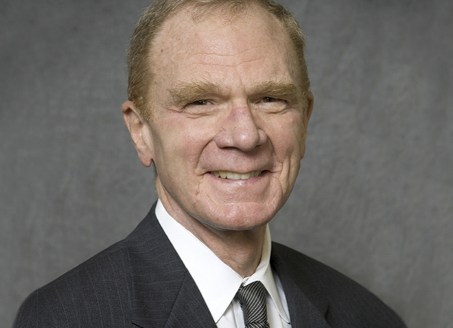 Braun in a suit in front of a gray background