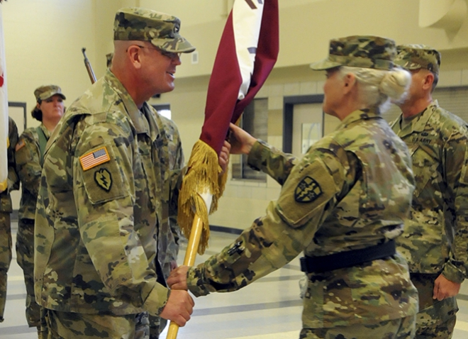 Nindl and a woman handing him a flag, both in military garb