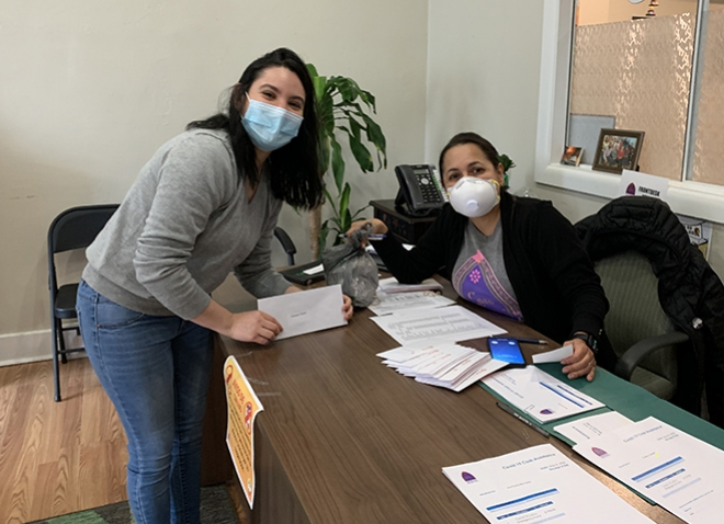 Two people in face masks, across a desk from one another