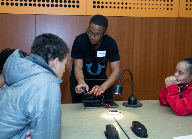 An instructor displays how to use a device for two pupils
