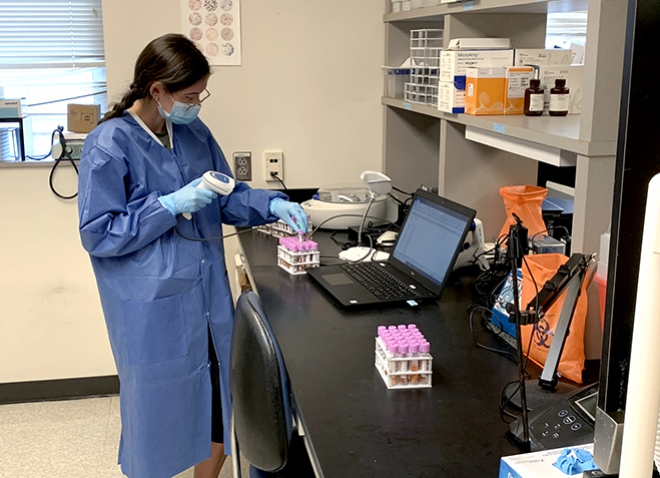 A person in a blue coat and gloves scans test tubes at a desk