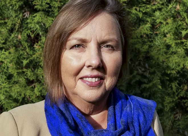 Headshot of Catherine Koverola, against background of greenery