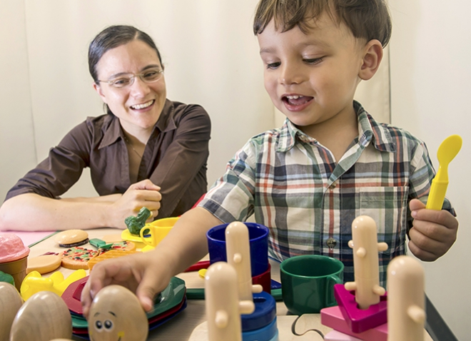 Libertus in a brown shirt and her 2-year-old Linus, playing with toys in a beige room
