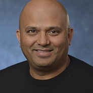 Neeraj Gandhi headshot wearing black crew neck