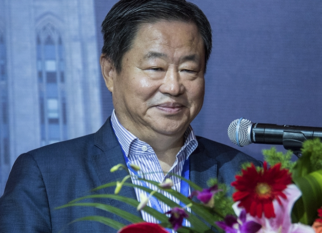 Frank Ning at microphone with flowers in foreground