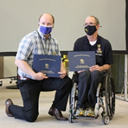 Garrett Grindle kneeling on the left and Rory Cooper in a wheelchair on the right.  Both hold up their Pennsylvania Veterans Service Awards.