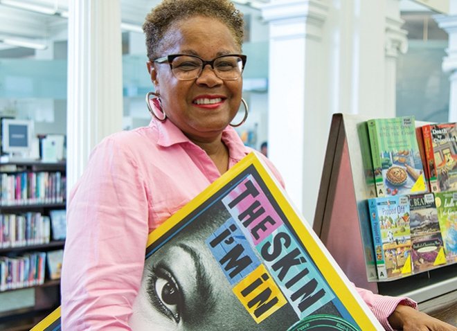 """Sharon Flake, holding oversized copy of her book """"The Skin I'm In,"""" standing in a library with shelves of books in the background"""