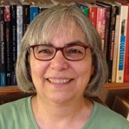 a woman in front of a bookcase in a green shirt
