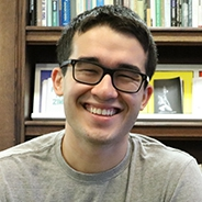 Starr, wearing a gray shirt and glasses, in front of a bookcase
