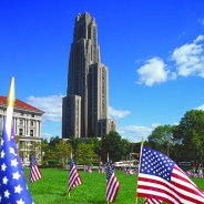 The Cathedral of Learning behind a field with small American flags standing upright