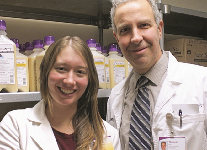 student Molly Westbrook and Hritz in front of a shelf of nutritional supplements, both wearing white coats