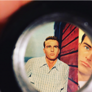 "Still image from ""Making Montgomery Clift"" film, showing a circular viewfinder with images of the actor standing against a red-planked wall"