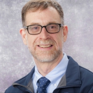 Waxman in a light blue shirt with a dark blue patterned tie and a blue coat in front of a purple background