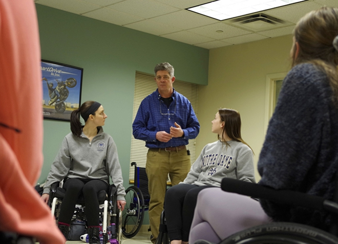 A person in a blue dress shirt and khaki pants speaking to four visible people in wheelchairs
