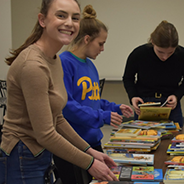 three young women packing a stack of books