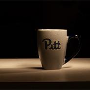 "A mug of coffee that says ""Pitt"" on it"