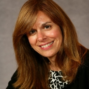 woman with reddish hair in a black sweater and black and white blouse