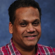 Datta in a red plaid shirt in front of a blue background