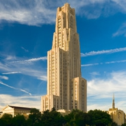 Cathedral of Learning against a blue sky with streaks of clouds.