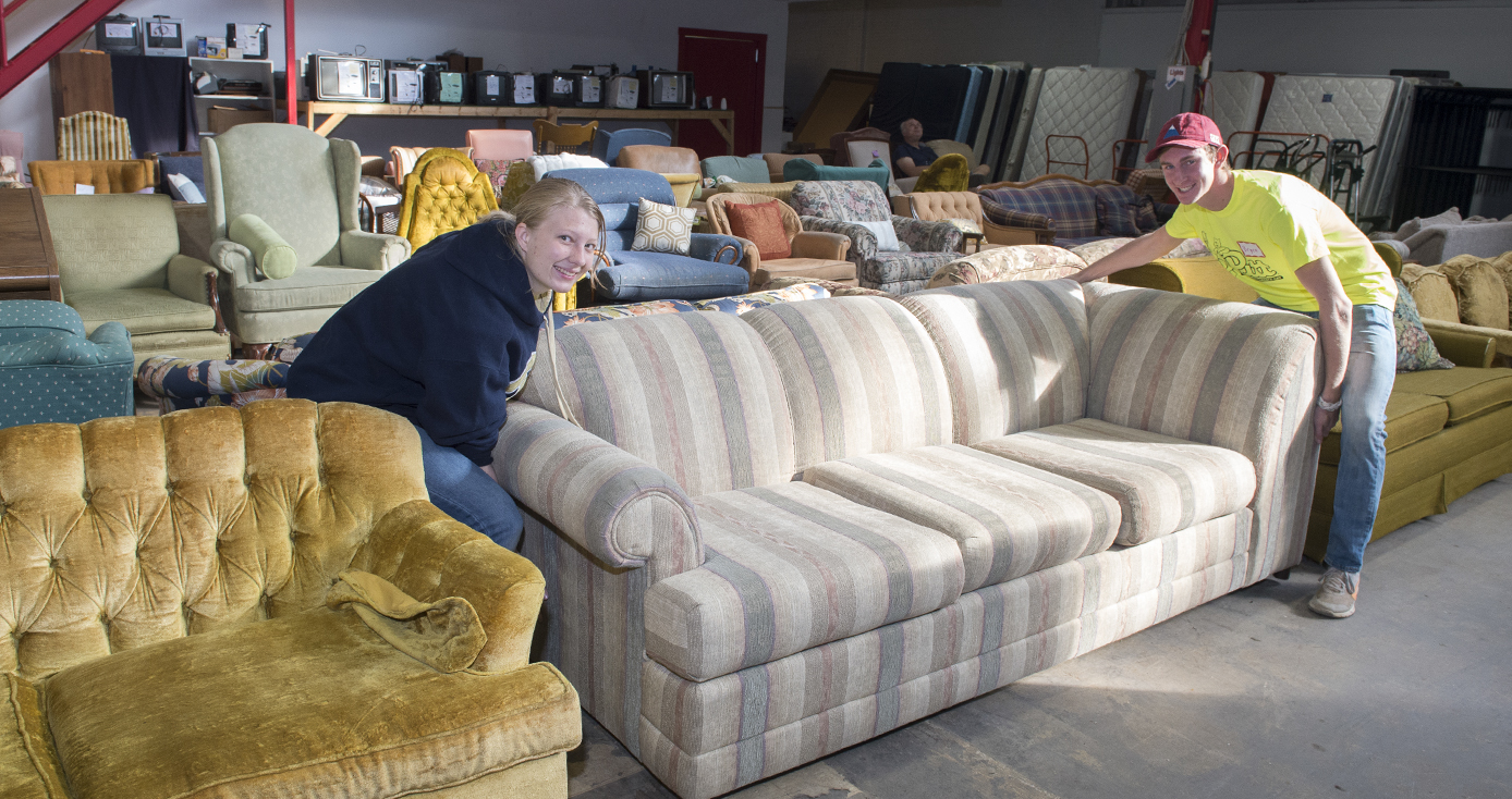 two students, a woman and a man, wearing neon yellow shirts and moving a couch