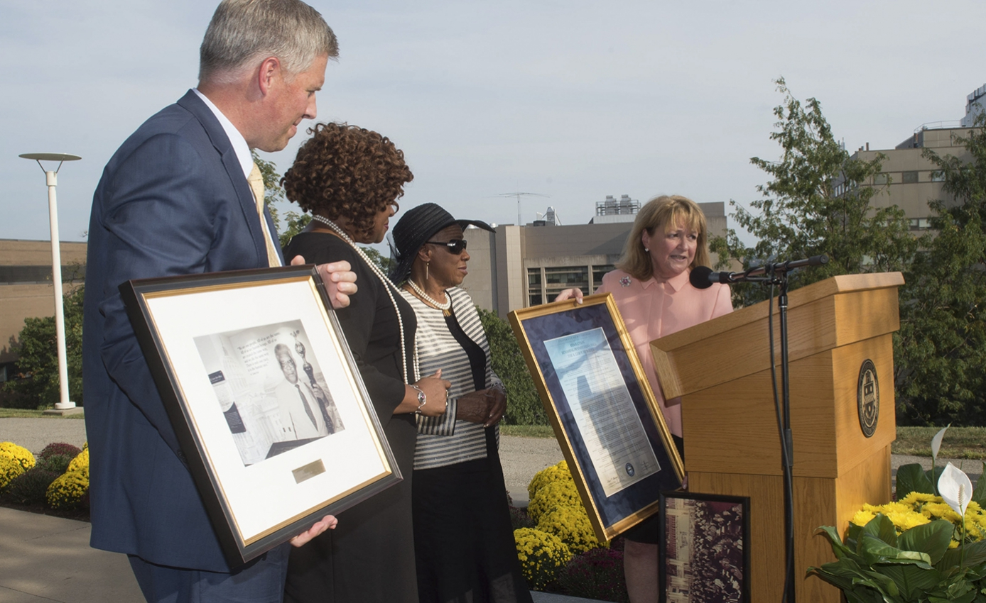 four people at podium with framed photograph and framed resolution