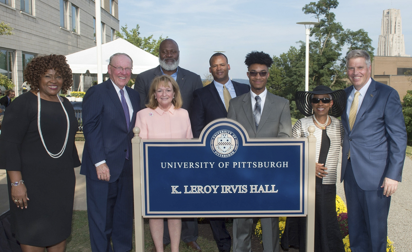 Eight people standing with K. Leroy Irvis Hall building sign
