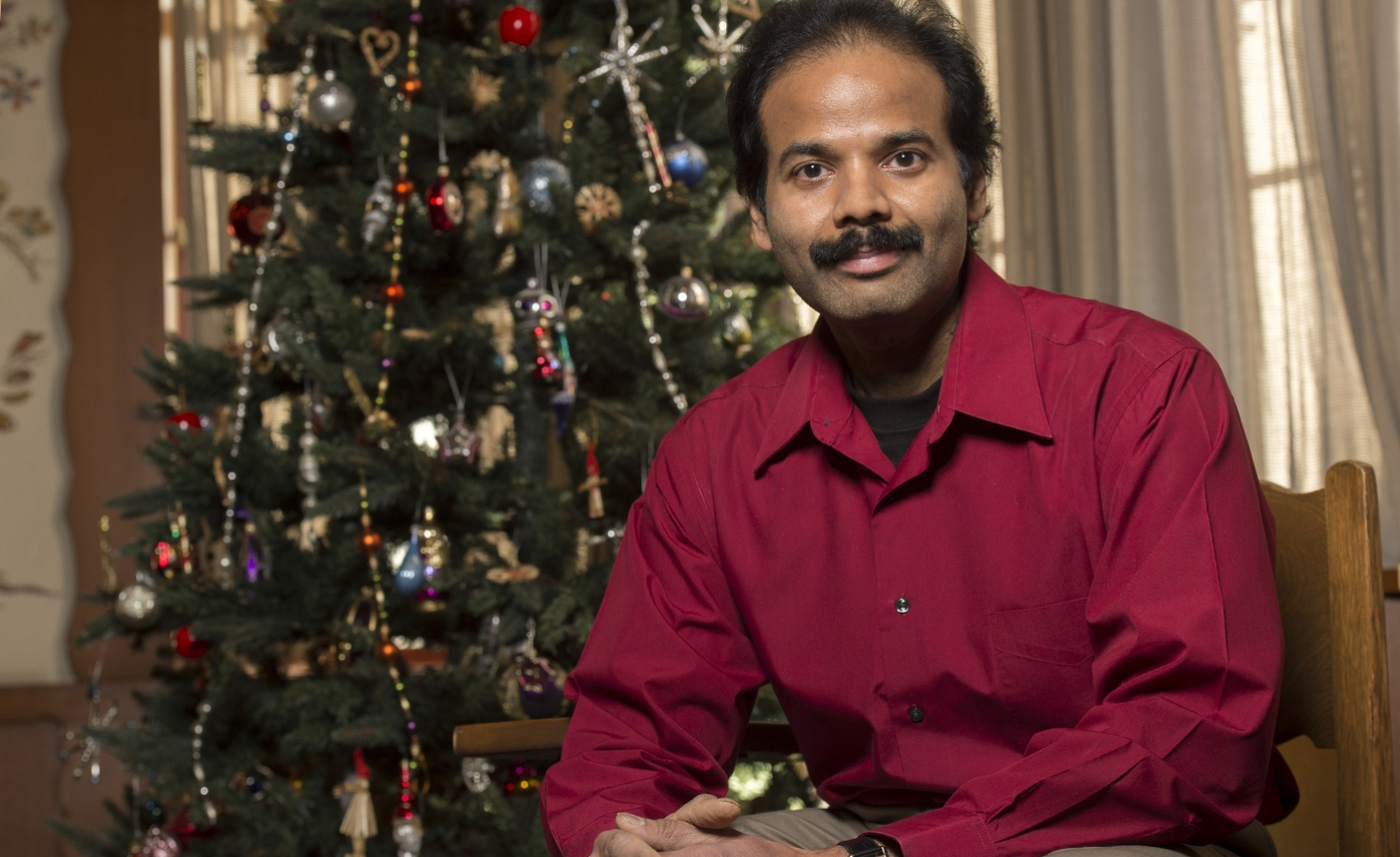 Senthil Natarajan sits in front of a Christmas tree