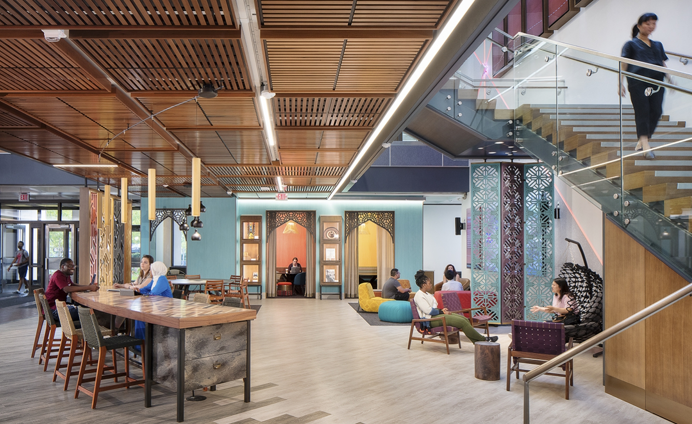 Global Hub space showing colorful walls and scree-dividers in a global art theme, stairwell and wooden desks and slatted wooden ceiling with students at tables, in charis