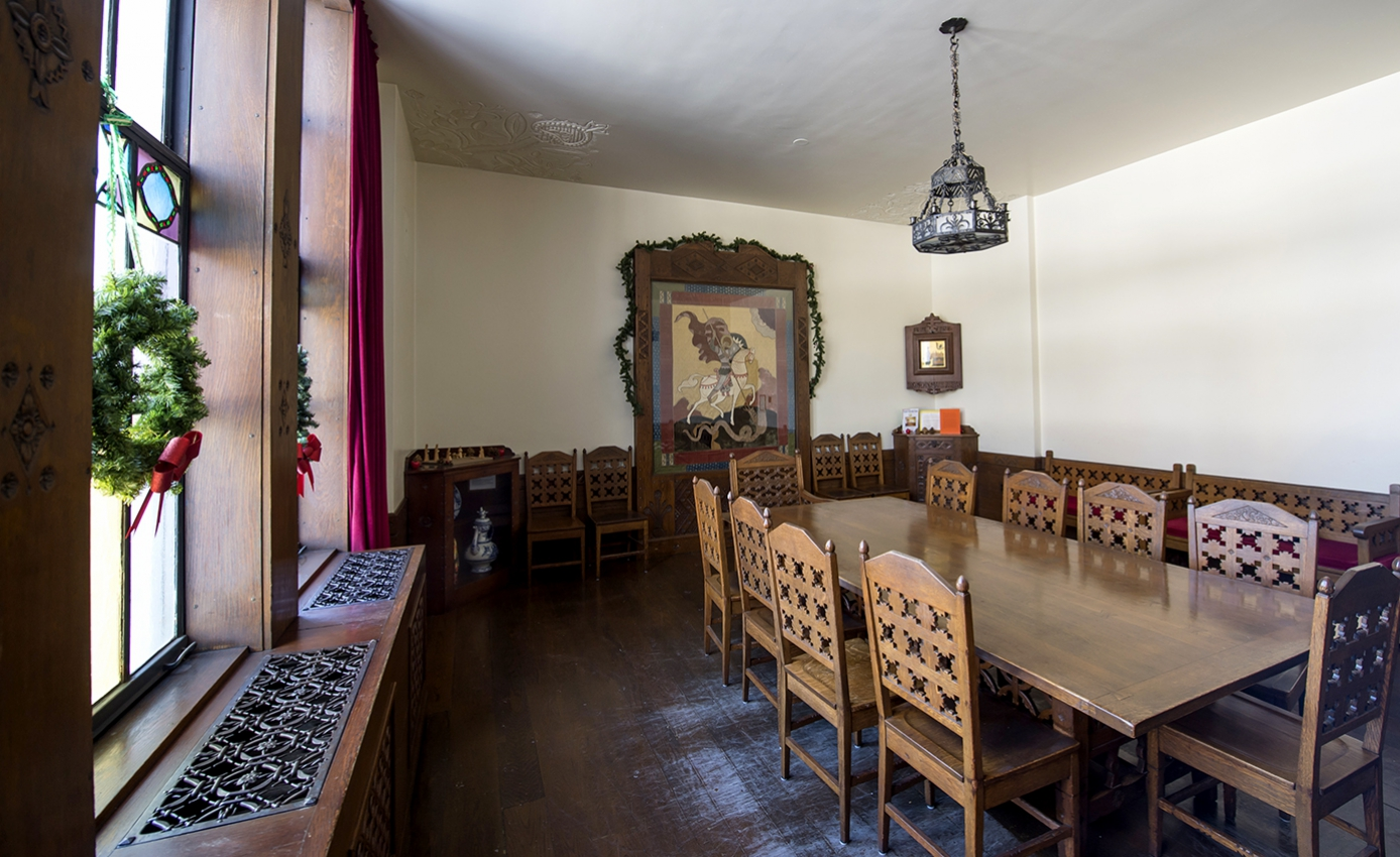 Wooden chairs around a rectangular table by wreath-decorated windows